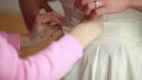 Weißes Hochzeitskleid, das auf dem Bett liegt stock footage