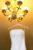 Weißes Hochzeitskleid, das am Leuchter hängt Lizenzfreie Stockfotos