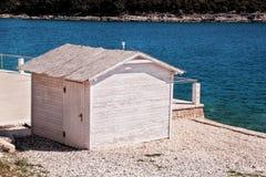 Weißes Holzhaus auf dem Strand durch das Meer Stockfotografie