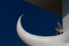 Weißes Horn, Elefantstoßzahn, weißer Halbmond mit tiefem blauem Himmel und Tempel im Hintergrund Stockfotos