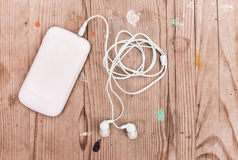 Weißes intelligentes Telefon mit Kopfhörern Stockbilder