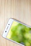 Weißes intelligentes Telefon mit lokalisiertem Schirm auf hölzernem Hintergrund Stockbild