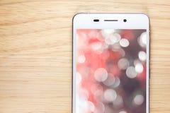 Weißes intelligentes Telefon mit Schirm auf hölzernem Hintergrund Stockfotografie