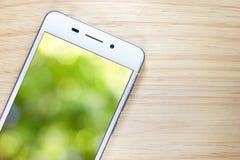 Weißes intelligentes Telefon mit Schirm auf hölzernem Hintergrund Lizenzfreies Stockfoto