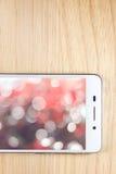 Weißes intelligentes Telefon mit Schirm auf hölzernem Hintergrund Lizenzfreies Stockbild