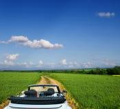Weißes Kabriolett auf einer Landstraße durch Felder lizenzfreie stockbilder