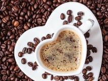 Weißes Kaffeetasseherz geformt mit cappucino Stockfotografie