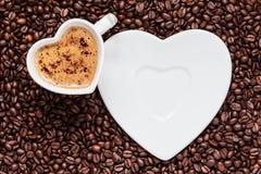 Weißes Kaffeetasseherz geformt mit cappucino Stockbilder