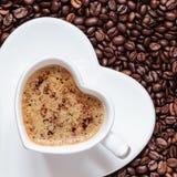 Weißes Kaffeetasseherz geformt mit cappucino Lizenzfreie Stockfotos