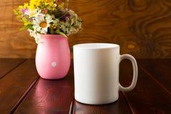 Weißes Kaffeetassemodell mit wilden Blumen lizenzfreie stockbilder