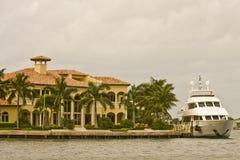 Weißes Kajütboot befestigt von Mansion Lizenzfreies Stockfoto
