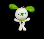 Weißes Kaninchen der handgemachten Häkelarbeit mit grüner Ohrpuppe auf schwarzem backg Stockfoto