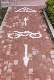 Weißes Kennzeichen des Fahrrades und des weißen Pfeiles, die eine Möglichkeit auf Asphaltweg zeigen Lizenzfreie Stockbilder