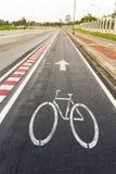 Weißes Kennzeichen des Fahrrades und des weißen Pfeiles, die eine Möglichkeit auf Asphaltweg zeigen Stockfotos