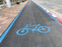 Weißes Kennzeichen des Fahrrades und des weißen Pfeiles, die eine Möglichkeit auf Asphaltweg zeigen stockfotografie