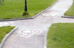 Weißes Kennzeichen des Fahrrades und des weißen Pfeiles, die eine Möglichkeit auf Asphaltweg zeigen Lizenzfreies Stockfoto