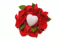 Weißes keramisches Herz, das auf dem Bett von rosafarbenen Blumenblättern und von Blättern O liegt Stockbilder