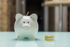Weißes keramisches Sparschwein mit Stapel von Münzen auf Glastisch stockfotografie