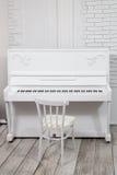 Weißes Klavier mit weißem Schemel vor einer weißen Backsteinmauer Stockfotografie