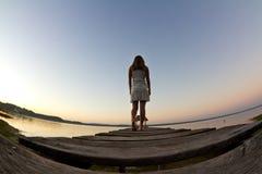 Weißes Kleid gegen einen schönen Sonnenaufgang Lizenzfreie Stockbilder