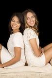 Weißes Kleid mit zwei Frauen auf Schwarzem zurück zu hinterem Lächeln Lizenzfreie Stockfotografie