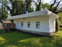 Weißes kleines Haus mit drei Fenstern im Holz Stockfoto