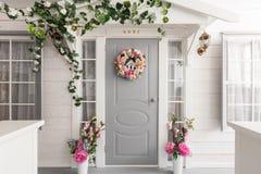 Weißes kleines Holzhaus mit grauer Tür Frühlingsblumendekoration Stockfoto