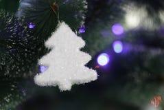 Weißes kleines Spielzeug auf einem großen Weihnachtsbaum mit einem unscharfen Blitz Stockbilder