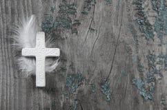 Weißes Kreuz mit Feder auf einem alten rustikalen Hintergrund Lizenzfreie Stockfotos