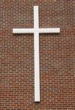 Weißes Kruzifix auf Backsteinmauer Lizenzfreies Stockbild
