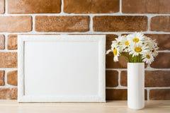 Weißes Landschaftsrahmenmodell mit Gänseblümchenblumenstrauß in angeredetem Vase Lizenzfreies Stockfoto