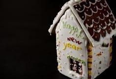 Weißes Lebkuchenhaus mit einem braunen Dach, einem Fenster und dem Aufschriftguten rutsch ins neue jahr auf einer weißen Wand stockfoto