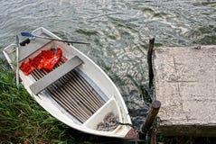 Weißes leeres Boot mit Rudern auf dem Wasser am Ufer lizenzfreies stockfoto