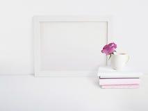 Weißes leeres Holzrahmenmodell mit einer Rosenblume in einer Porzellanschale und in einem Stapel von den Büchern, die auf dem Tis Stockfoto