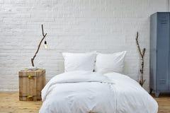 Weißes Leinen und Birkenzweige des Dachbodenatmosphärenschlafzimmers Lizenzfreies Stockfoto
