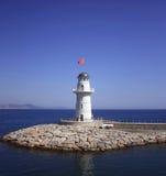Weißes Leuchtfeuer nahe Küste mit einer roten Fahne Stockbild