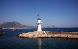 Weißes Leuchtfeuer nahe Küste mit einer roten Fahne Stockfoto