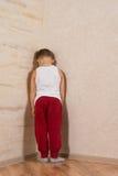Weißes Little Boy, das hölzerne Wände gegenüberstellt Stockbild