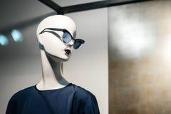 Weißes Mannequin weiblich in den blauen modernen Gläsern und im Kleid stockbilder