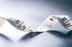 Weißes messendes Band auf einem dunklen Hintergrund Gerolltes Band mit Zahlen Stockbilder