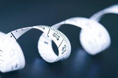 Weißes messendes Band auf einem dunklen Hintergrund Gerolltes Band mit Zahlen Stockfoto