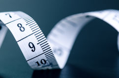 Weißes messendes Band auf einem dunklen Hintergrund Gerolltes Band mit Zahlen Lizenzfreie Stockfotos