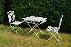 Weißes Metallgartenmöbeltabelle und zwei Stühle Stockfotos