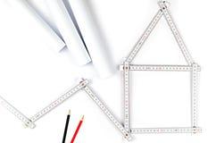 Weißes Meterwerkzeug, das ein Haus, zwei zeichnende Bleistifte und Papier bildet Lizenzfreie Stockfotografie