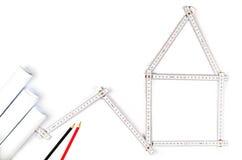 Weißes Meterwerkzeug, das ein Haus, zwei zeichnende Bleistifte und Papier bildet Lizenzfreies Stockfoto