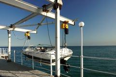 Weißes Motorboot, das an Pier Davit hängt Stockfotografie