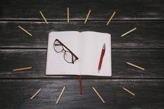 Weißes Notizbuch, Stift und Gläser und viele Bleistifte auf einem schwarzen hölzernen Hintergrund Lizenzfreie Stockfotografie