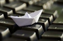 Weißes origami Boot auf Tastatur Stockfotografie