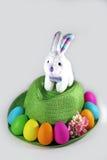 Weißes Ostern-Häschen auf einem grünen Strohhut mit bunten Eiern Ostern Lizenzfreie Stockbilder
