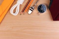 Weißes Pfadfinderseil der Ordnung, Schal, Pfeife, Bleistift, Kompass und rotes Barett Stockfotografie